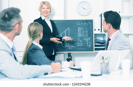 Successful smiling business woman presenting new business strategy to partners in office