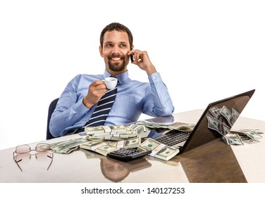 Successful smiling businessman relaxing and drinking coffee with a lot of dollar stacks at the desk isolated on white background