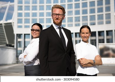 Successful smiling businessman in suit standing in front of his colleagues. Smiling businesswomen in white shirts posing with arms crossed.