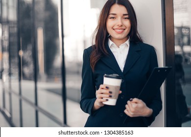 Successful smiling businesswoman or entrepreneur drink coffee in front of his office.