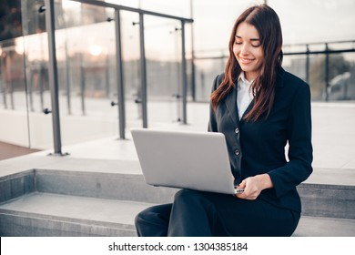 Successful smiling businesswoman or entrepreneur using laptop sitting in front of his office.