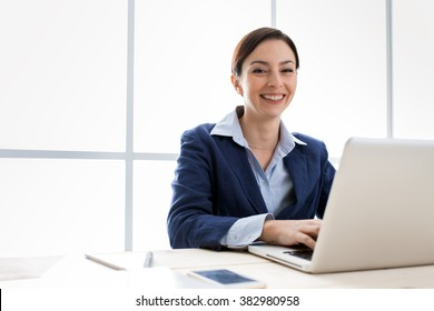 Successful smiling businesswoman posing in her office, she is sitting at desk and working with a laptop, women's entrepreneurship concept