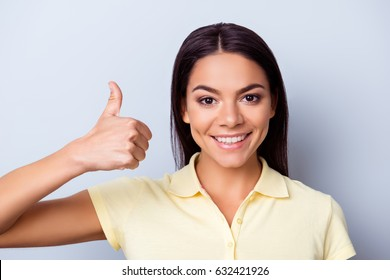 Successful smiling latino girl is showing like sign on light blue background