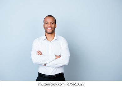 Successful smiling young handsome mulatto american guy banker in formal outfit on pure background with crossed hands. So rich and confident, attractive and smart