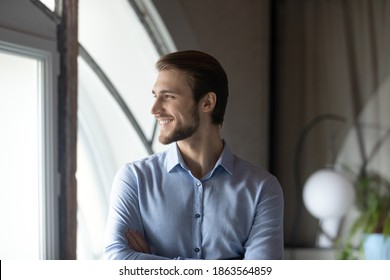 Successful smiling young man corporate employee boss team leader satisfied with professional achievements career growth standing close to window looking forward creating business vision strategy plan