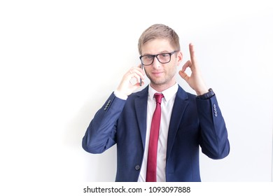 Successful, smilling businessman showing OK sign by his hands in the office. Satisfied with great development rate, business growth, company success concept.