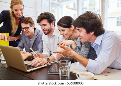 Successful start-up team with laptop in training full of joy