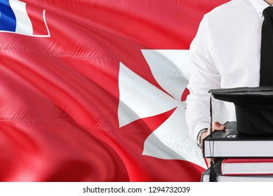 Successful student education concept. Holding books and graduation cap over Wallis And Futuna flag background.