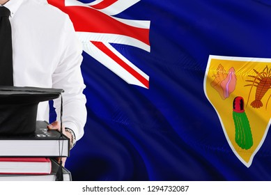 Successful student education concept. Holding books and graduation cap over Turks And Caicos Islands flag background.