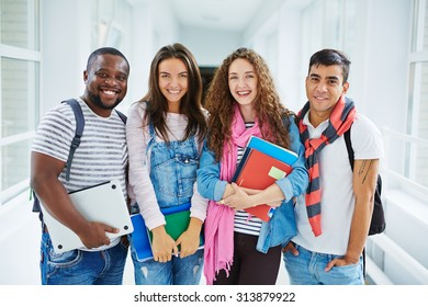 Successful students looking at camera in college corridor
