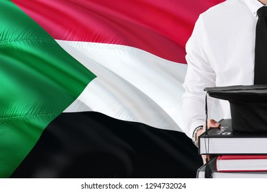 Successful Sudanese student education concept. Holding books and graduation cap over Sudan flag background.