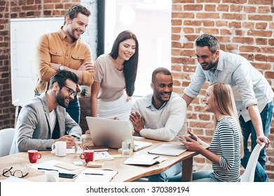 Successful team. Group of cheerful young people discussing something with smile and gesturing while leaning to the table in office
