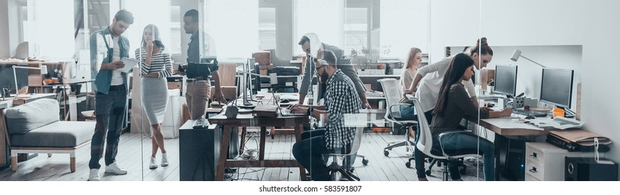 Successful team. Group of young business people working and communicating together in creative office - Shutterstock ID 583591807
