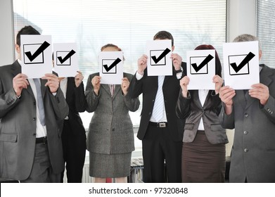 Successful team holding check mark vote sign