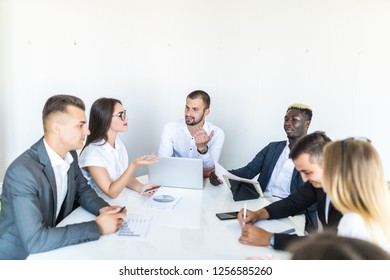 Successful team leader and business owner leading informal in-house business meeting. Businessman working on laptop in foreground.
