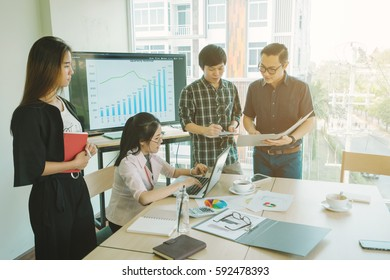Successful team leader and business owner leading informal in-house business meeting. Businessman working on projecter showing sucessful graph. Business and entrepreneurship concept.