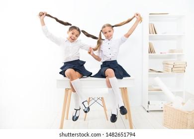 Successful team. Little schoolgirls classmates kids. Schoolgirls friends sit on desk. Best friends relaxing. Schoolgirls tidy hairstyle relaxing having rest. School uniform. Rebellious spirit.