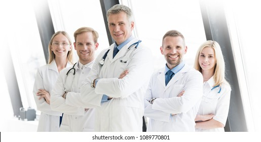 Successful team of medical doctors are looking at camera and showing thumbs up