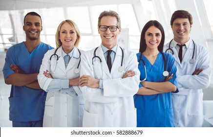 Equipe bem sucedida de médicos estão olhando para câmera e sorrindo enquanto está no hospital