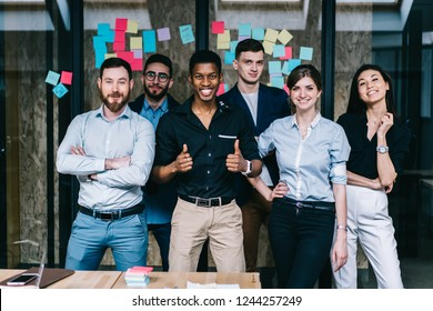 Successful team of multicultural young people dressed in formal wear smiling and showing ok at camera.Prosperous group of male and female diverse professionals standing in modern office interior