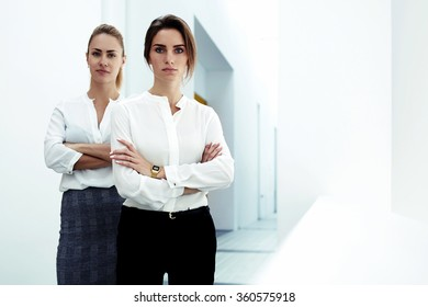 Successful team of young reliable women leaders dressed in formal wear posing together in modern office, confident two female with a serious look standing with crossed arms in big company hallway