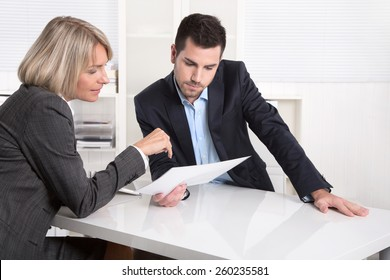 Successful teamwork: business man and woman sitting at desk talking about reports and finance.