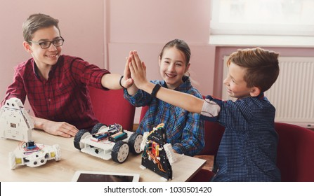 Successful teamwork. Children giving group high-five after creating robots at school, stem education. Early development, diy, innovation, modern technology concept