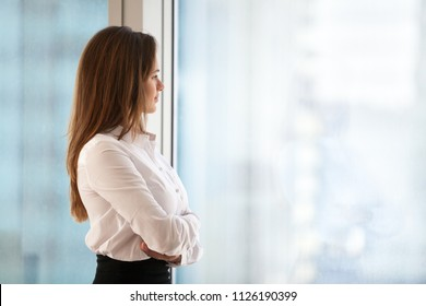 Successful thoughtful woman business leader looking out of big window enjoying city view and wellbeing feeling motivated for new goals, rich millennial businesswoman dreaming of future, copy space