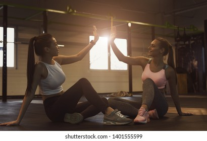 Successful training. Women giving high five, having rest in gym