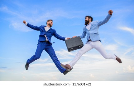 Successful transaction between businessmen. Briefcase handover in heaven blue sky background. Easy deal business. Businessmen jump fly mid air while hold briefcase. Case with raise your business.