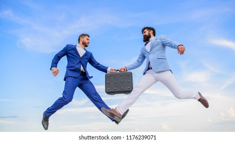 Successful transaction between businessmen.Easy deal business. Businessmen jump fly mid air while hold briefcase. Case with raise your business. Briefcase handover in heaven blue sky background.
