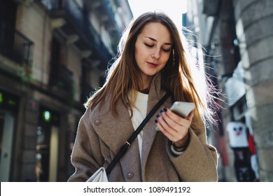 Successful travel blogger checking email box on mobile phone app while walking the city. Charming female wearing stylish outfit chatting online with friends by a smartphone connected to wifi.