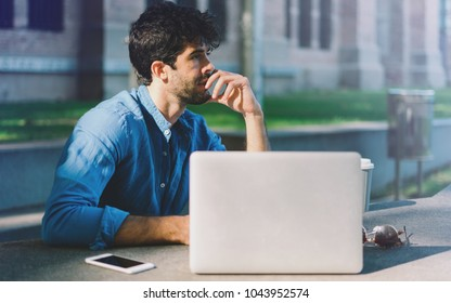 Successful travel blogger planning the journey to the asian countries while sitting outside with a laptop. Thoughtful bearded man looking aside while sitting in a park with gadgets.