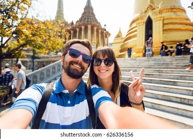 Successful traveling couple in love taking a selfie on phone  at Grand Palace temples in Bangkok  Pretty girl and her handsome boyfriend with beard having fun, crazy emotional faces , laughing.