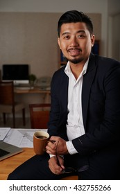 Successful Vietnamese businessman with big mug of coffee