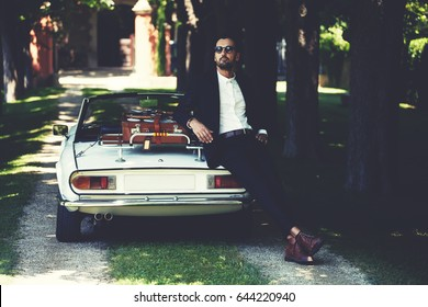 Successful and wealthy businessman enjoying a day during trip on luxury cabriolet car on countryside road, sure and confident handsome man with his new convertible car and villa house on background