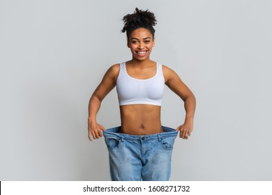 Successful weight loss, afro woman with too large jeans after effective diet, grey background