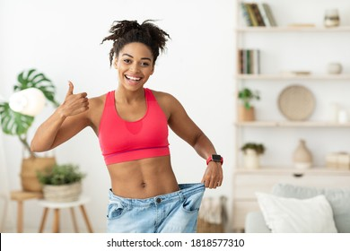 Successful Weight Loss. Slim African American Lady Gesturing Thumbs Up Approving Diet Wearing Old Too Big Jeans Standing At Home
