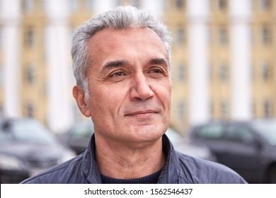 A successful well-groomed man over 50 years, short gray hair, a pleased look, casual clothes, the face of a politician, TV presenter or doctor. Middle-aged man with delicate features, smart appearance