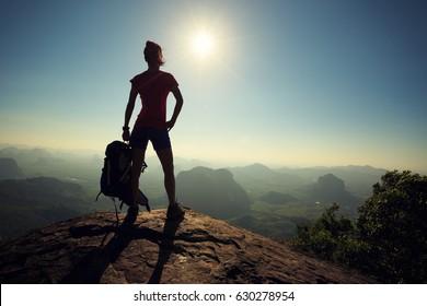 successful woman backpacker hiking on sunrise mountain top