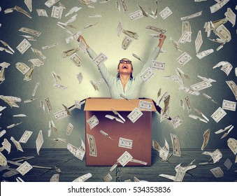 Successful woman coming out from a box under money rain. Financial success concept