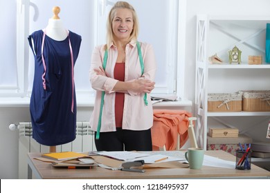 Successful woman designer clothes, tailor in studio in full growth. Beautiful woman looking at the camera, standing near table in the workshop with clothes.
