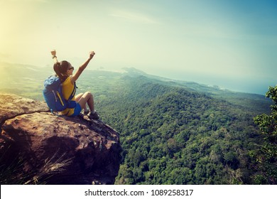 successful woman hiker cheering on mountain peak cliff edge
