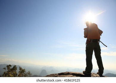 successful woman hiker enjoy the view at sunrise mountain peak