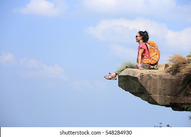 successful woman hiker enjoy the view on mountain top rock edge