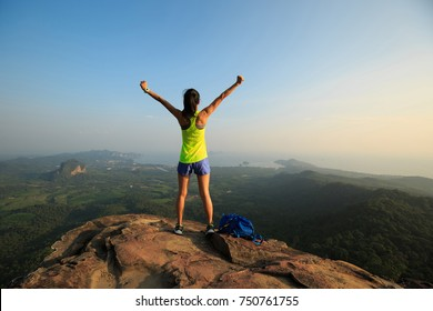 successful woman hiker enjoy the view on cliff edge top of mountain