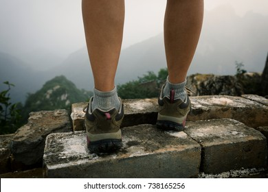 successful woman hiker legs on the top of great wall