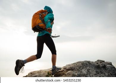 Successful woman hiker running to on seaside mountain peak cliff edge