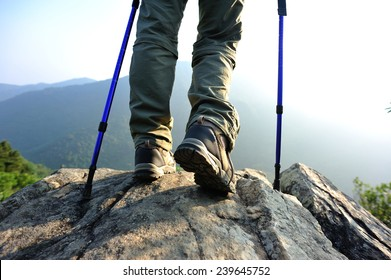 Successful woman hiker stand on mountain peak rock enjoy the view