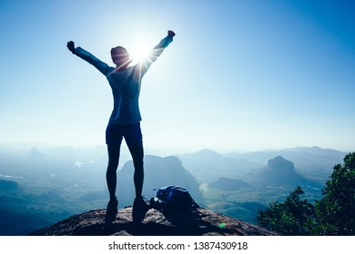 Successful woman hiker in the sunrise mountain top